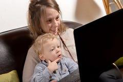 Jeune mère et son enfant regardant un ordinateur Photos libres de droits