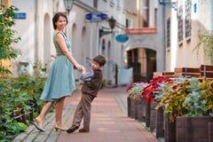 Jeune mère et son fils marchant à l'extérieur dans la ville Photographie stock libre de droits