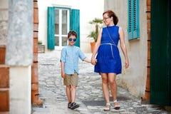 Jeune mère et son fils marchant à l'extérieur dans la ville Photos stock