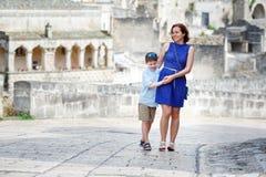 Jeune mère et son fils marchant à l'extérieur dans la ville Image stock