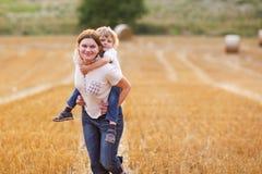 Jeune mère et son petit fils ayant l'amusement sur le gisement jaune de foin Image stock
