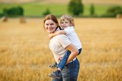 Jeune mère et son petit fils ayant l'amusement sur le gisement jaune de foin Photo libre de droits