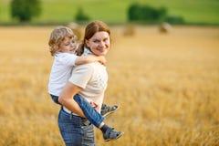Jeune mère et son petit fils ayant l'amusement sur le gisement jaune de foin Photographie stock libre de droits