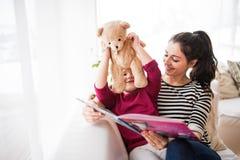 Jeune mère et une petite fille avec l'ours de nounours à la maison, lisant un livre Photographie stock libre de droits