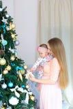 Jeune mère européenne tenant la fille dans des bras et la position près de l'arbre de hristmas, robe rose de port photographie stock libre de droits