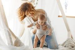 Jeune mère gaie riant et jouant avec le fils mignon nouveau-né dans la chambre à coucher légère confortable dans le matin L'atmos Image stock