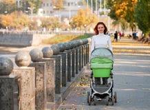 Jeune mère heureuse avec la chéri dans la poussette Photographie stock
