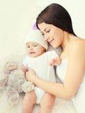 Jeune mère heureuse avec le bébé ensemble sur la maison de lit, vue supérieure Image libre de droits