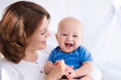 Jeune mère heureuse avec le bébé garçon à la maison Photo libre de droits