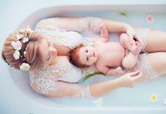 Jeune mère heureuse avec le bébé nouveau-né, fille dans le bain floral de lait photos stock