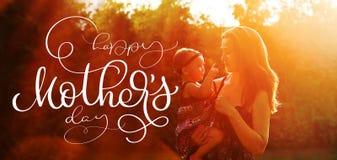 Jeune mère heureuse avec le jour de mères heureux de fille et de textes Aspiration de main de lettrage de calligraphie Photos stock