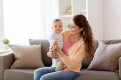 Jeune mère heureuse avec le petit bébé à la maison Images stock