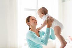 Jeune mère heureuse avec le petit bébé à la maison Photo stock