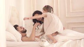 Jeune mère heureuse et petite fille réveillant le père un matin ensoleillé clips vidéos