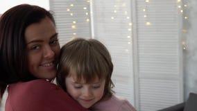Jeune mère heureuse et ses petits regards de fille à un appareil-photo banque de vidéos