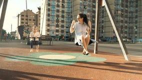 Jeune mère heureuse et son petit fils balançant au terrain de jeu d'enfants du secteur de dortoir, au coucher du soleil de soirée banque de vidéos