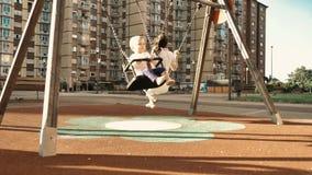 Jeune mère heureuse et son petit fils balançant au terrain de jeu d'enfants du secteur de dortoir, au coucher du soleil de soirée clips vidéos