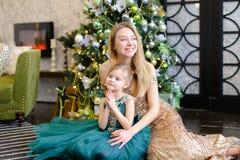 Jeune mère heureuse européenne et petite fille avec la lumière de Bengale se reposant sur le plancher près de l'arbre de Noël photos stock