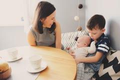 Jeune mère heureuse prenant le petit déjeuner dans la cuisine moderne avec son fils de fille et d'enfant de bébé Photo stock