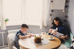 Jeune mère heureuse prenant le petit déjeuner dans la cuisine moderne avec son fils de fille et d'enfant de bébé Image stock