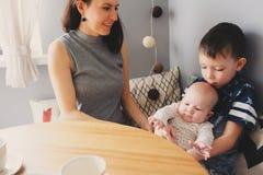 Jeune mère heureuse prenant le petit déjeuner dans la cuisine moderne avec son fils de fille et d'enfant de bébé Photo libre de droits