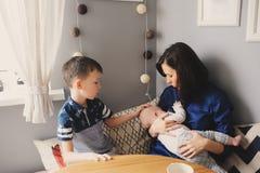 Jeune mère heureuse prenant le petit déjeuner dans la cuisine moderne avec son fils de fille et d'enfant de bébé Photos stock