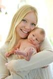 Jeune mère heureuse tenant le bébé nouveau-né câlin Images libres de droits