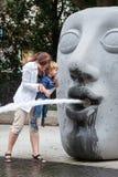 Jeune mère jouant avec le garçon d'enfant en bas âge avec de l'eau de fontaine Image stock