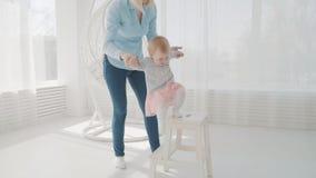 Jeune mère jouant avec sa fille près de la chaise Famille heureux Mouvement lent banque de vidéos