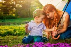 Jeune mère jouant avec son petit fils dans le jardin Concept de jour du ` s de mère Photographie stock
