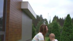 Jeune mère jouant et ayant l'amusement avec ses frères de fils de bébé garçon dans un jardin avec des jouets - couleur chaude de  clips vidéos