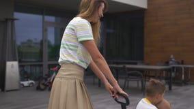 Jeune mère jouant et ayant l'amusement avec ses frères de fils de bébé garçon dans un jardin vert avec des voitures - valeurs fam clips vidéos