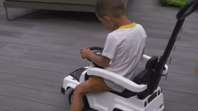 Jeune mère jouant et ayant l'amusement avec ses frères de fils de bébé garçon dans un jardin vert avec des voitures - valeurs fam banque de vidéos