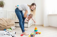 Jeune mère la tenant pleurant 10 mois de bébé garçon Photos stock