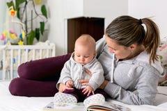 Jeune mère, lisant un livre à son bébé garçon, lui montrant le pictur image stock