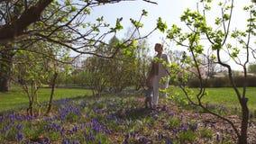 Jeune mère marchant avec un fils de bébé garçon sur une jacinthe de raisin de champ de muscari au printemps - jour ensoleillé - clips vidéos
