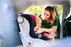 Jeune mère mettant le bébé garçon dans le siège de voiture Image libre de droits