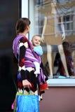 Jeune mère mignonne avec la chéri dans l'élingue photographie stock