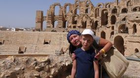 Jeune mère montrant à l'amphithéâtre antique de fille Gordian en EL Jem Tunisia banque de vidéos