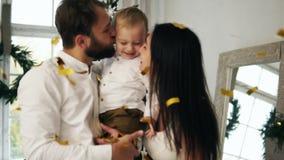 Jeune mère, père et leur petit fils célébrant avec des confettis de tir le réveillon de Noël à la maison, baisers leurs clips vidéos