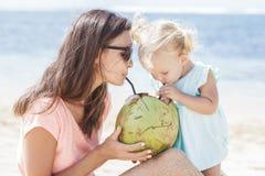 Jeune mère partageant l'eau de noix de coco avec sa fille tandis qu'appréciez images stock