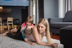 Jeune mère passant le temps avec des enfants sur le plancher Photographie stock libre de droits