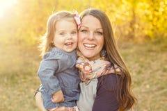 Jeune mère portant sa fille mignonne de sourire dehors Photographie stock libre de droits