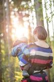 Jeune mère portant son bébé garçon sur une promenade Photographie stock libre de droits