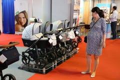 Jeune mère regardant des chariots à bébé Photographie stock libre de droits