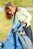 Jeune mère riante regardant dans la poussette Images stock