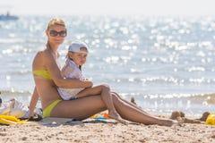 Jeune mère s'asseyant avec la vieille fille de cinq ans congelée sur la plage Image libre de droits