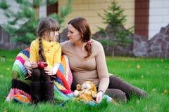 Jeune mère s'asseyant avec le descendant sur une pelouse Image libre de droits