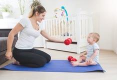 Jeune mère s'exerçant à la maison donnant l'haltère à ses 9 mois de bébé garçon Images stock