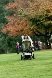Jeune mère se penchant au-dessus d'une poussette ou d'une poussette image libre de droits